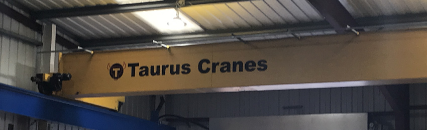 An overhead crane installed by Taurus Cranes, with a Taurus Cranes graphic on the side.